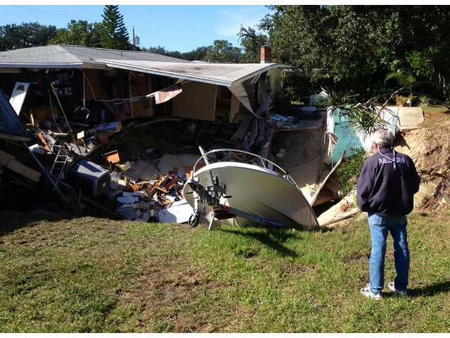 A man observes a sinkhole has swallowed parts of two houses in Dunedin, Fla. on Thursday.