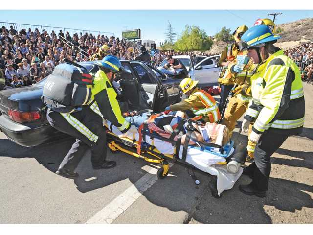 Mock collision victim and Canyon High student Sage Walsh, 16, is removed from the wreckage of a simulated car collision due to drunk driving in front of Canyon High School during the Every 15 Minutes program on Thursday. Photo by Dan Watson.