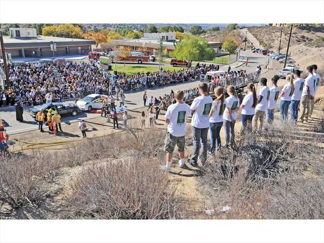 Canyon High students representing the young drivers that die every 15 minutes in DUI-related car crashes look down on the scene of the mock accident. Photo by Dan Watson.