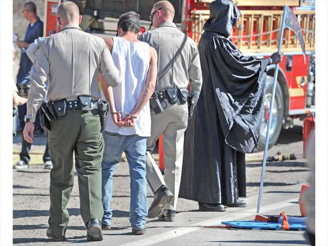 "A Canyon High student is ""arrested"" by a Santa Clarita Sheriff's Deputy as they walk past the Grim Reaper, right, at the scene of a simulated car collision due to drunk driving in front of Canyon High School. Photo by Dan Watson."