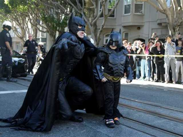 "Miles Scott, dressed as Batkid, right, walks with Batman before saving a damsel in distress in San Francisco, Friday, Nov. 15, 2013. San Francisco turned into Gotham City on Friday, as city officials helped fulfill Scott's wish to be ""Batkid."""