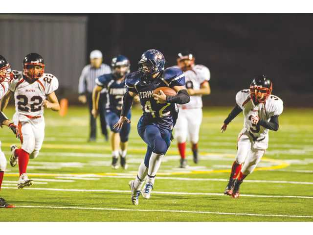 Trinity Classical Academy running back Patch Kulp (42) runs away from Noli Indian defenders on Friday at College of the Canyons.