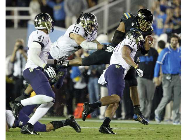 UCLA quarterback Brett Hundley dives for extra yards against Washington on Friday night.