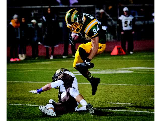Canyon Running back Elijah Williams leaps over a West Torrance defender for a touchdown at Canyon High School on Friday.