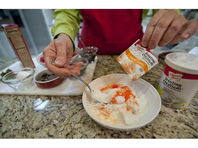 Merry Graham pours Duncan Hines Orange Crème mix into her signature tart filling.