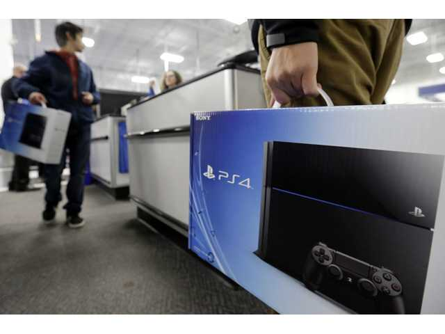 A man holds a Sony PlayStation 4 after he purchased it at the Lincoln Park Best Buy store in Chicago on Friday.