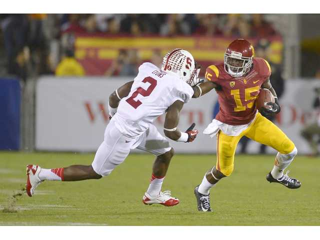 Trojans receiver Nelson Agholor (right) stiff arms Stanford cornerback Wayne Lyons during the first half of Saturday's game.