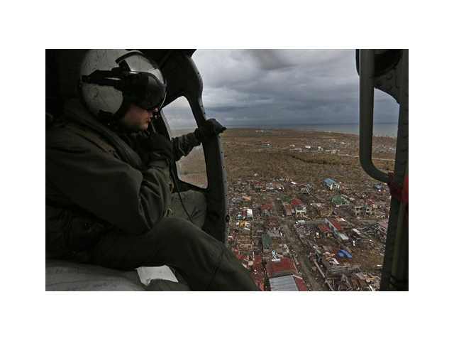 A crew member of a U.S. Navy Sea Hawk helicopter from the U.S. aircraft carrier USS George Washington looks at the devastation caused by Typhoon Haiyan near the coastal town of Tanawan, central Philippines Sunday.