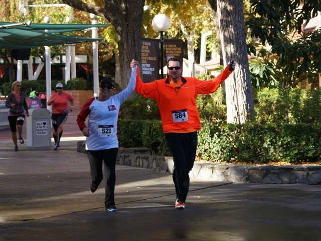 A pair of runners holds hands as they jog along the course at Sunday's HandsOn Santa Clarita race. Photo by Jim Holt.