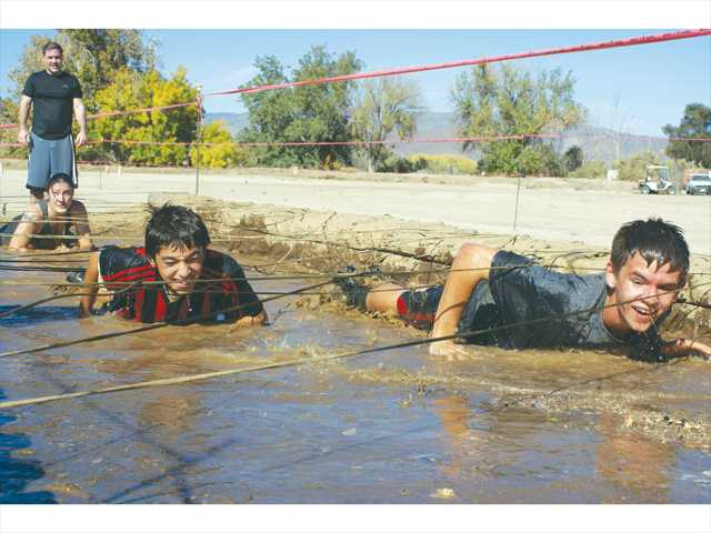 Brothers Zack, right, and Alek Kaufman, 15 and 11, crawl through the muck of one of the courses at the Getting Dirty for Charity mud run in Acton on Sunday. Photo by Jim Holt.