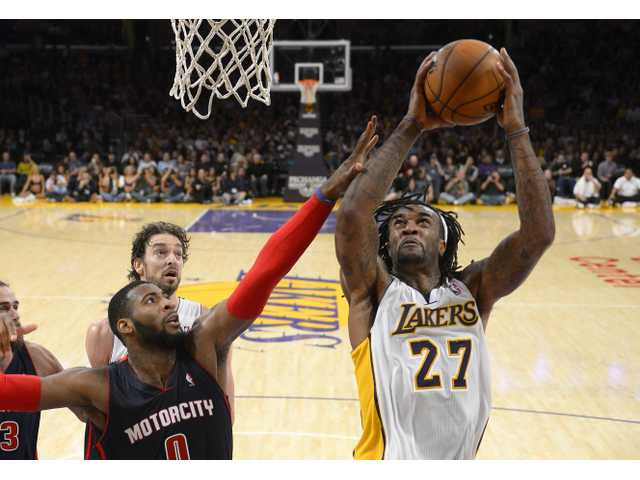 Los Angeles Lakers center Jordan Hill, right, puts up a shot as Detroit Pistons center Andre Drummond, lower left, defends.