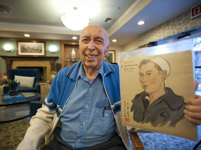 Navy veteran Robert Werkmeister poses with an illustration a Japanese artist drew of him at the Summerhill Villa retirement community, which erected a Wall of Honor to thank local service men and women for their sacrifice. Signal photo by Charlie Kaijo