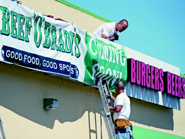 Beef 'O' Brady's restaurant officially closed its doors on Monday. Above, Kevin Jackson, top, and Brian Valladares hung a temporary banner announcing the July 2 opening of the new restaurant on The Old Road in Valencia.