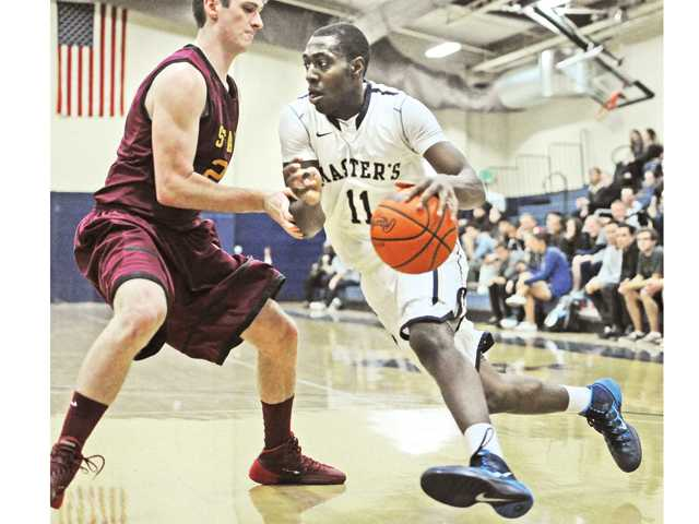 The Master's College's Jason Logan (11) drives under the basket against Claremont's Jason Harrington at TMC on Tuesday.