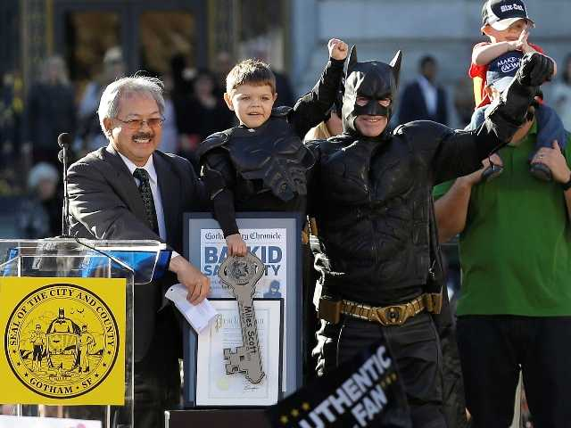 Miles Scott, dressed as Batkid, second from left, raises his arm next to Batman at a rally outside of San Francisco City Hall in San Francisco, Friday, Nov. 15.
