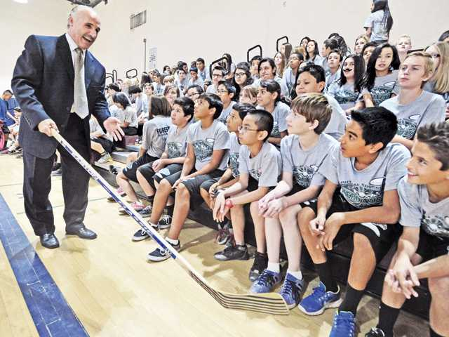 L.A. Kings radio commentator Daryl Evans demonstrates the use of the hockey stick for seventh and eighth-grade P.E. students in the Sierra Vista Junior High School gym in Canyon Country on Wednesday. Photo by Dan Watson.