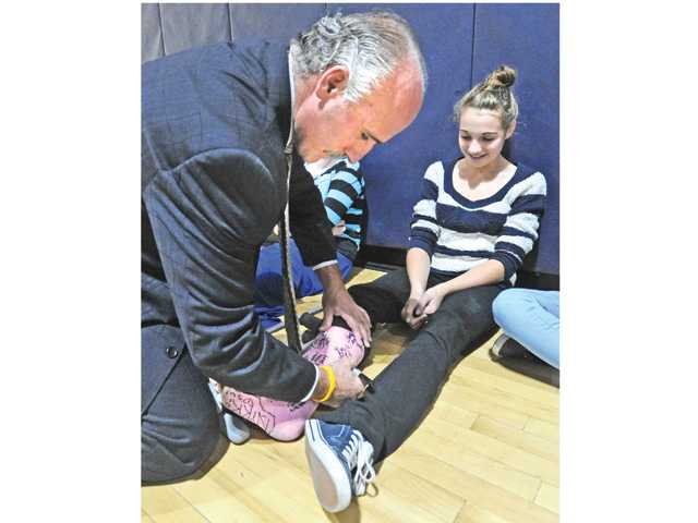 L.A. Kings radio commentator Daryl Evans autographs the leg cast of Sierra Vista Junior High seventh-grader Katie Benavidez. Photo by Dan Watson.