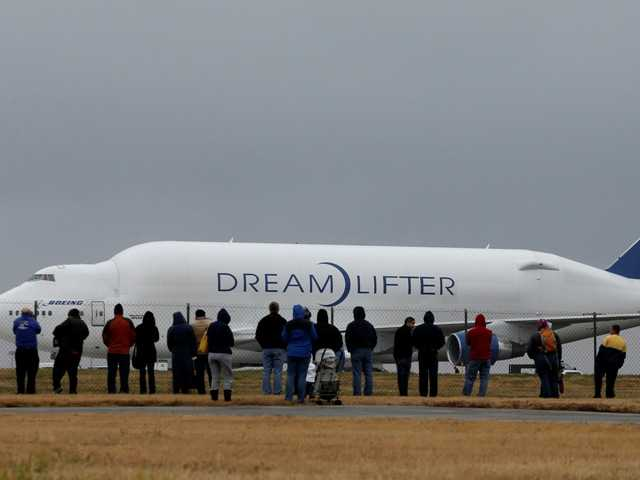 "Onlookers watch a Boeing 747 ""Dreamlifter"" as it sits on a runway Thursday, the day after it mistakenly landed at the wrong airport, 8 miles off it's intended course."
