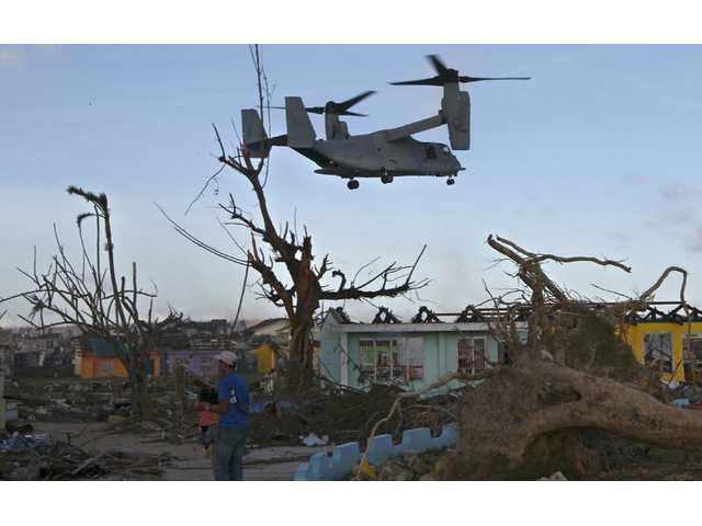 In this Nov. 14 file photo, a U.S. Marine MV-22 Osprey aircraft flies over damaged buildings as it prepares to land to deliver relief goods for typhoon survivors in Guiuan, Philippines.