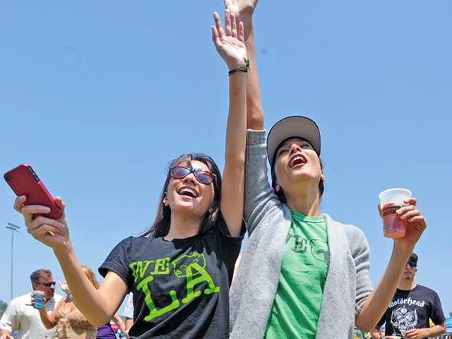 Jennifer Green, left, and Misa Chien sing along at the 2nd annual Tributefest concert at Central Park. Dan Watson/The Signal
