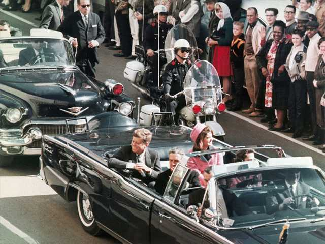 In this Nov. 22, 1963 file photo, President John F. Kennedy's motorcade travels through Dallas, Texas.