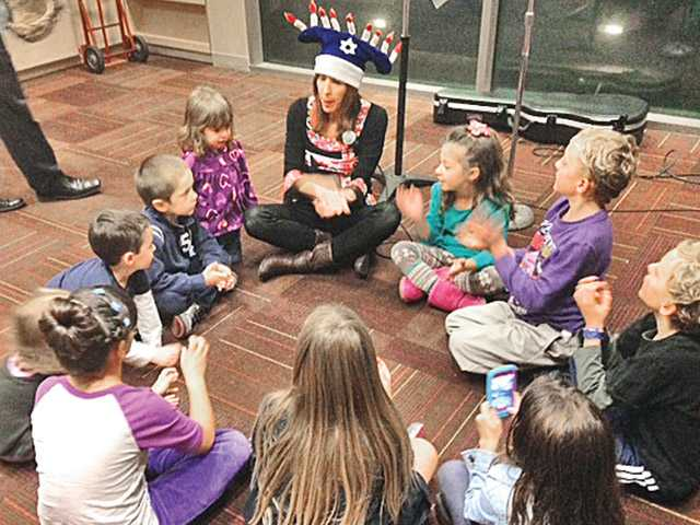 Wendy Hersh, local musician and Temple Beth Ami member, performed for the children during story time. Hersh sang and played instruments during several songs for the Hanukkah story time event.