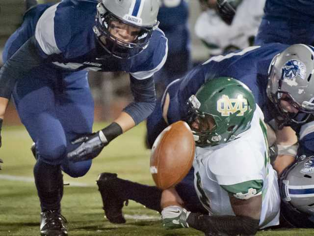 Saugus lineman Steven Kwak, left, tries to recover the ball after Mira Costa running back Sebastian Franck-Love is stripped during Friday's CIF-Southern Section Northern Division playoff game at Canyon High School.