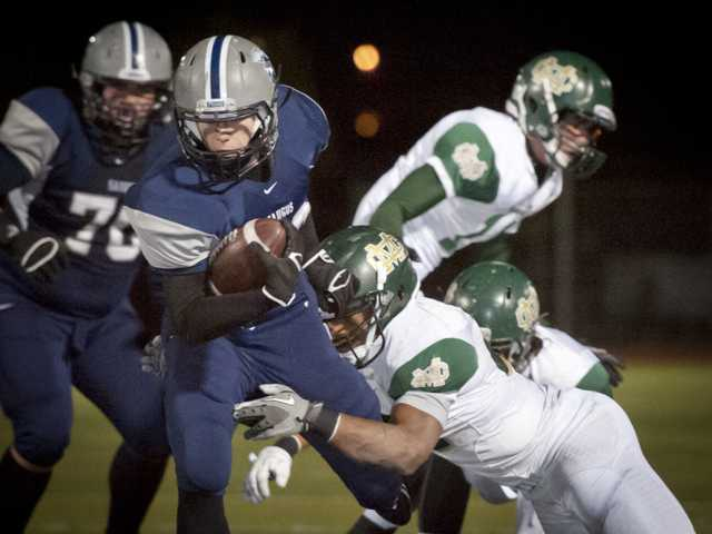 Saugus running back Reid Rupe runs the ball past Mira Costa defenders on Friday night at Canyon High School.