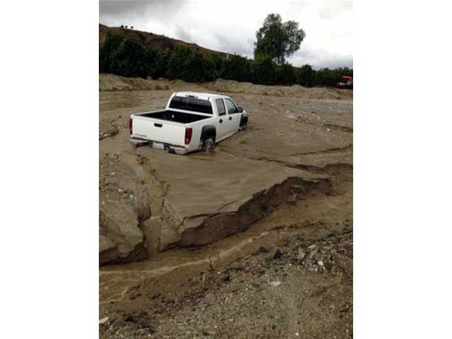 This Nov. 21, 2013 photo released courtesy City of Redlands shows flooding, mud and debris on San Timoteo Canyon Road in Redlands, Calif. Firefighters responded to dozens of calls of weather-related traffic collisions, flooding and mudslides spurred by Thursday's downpour in southern California.