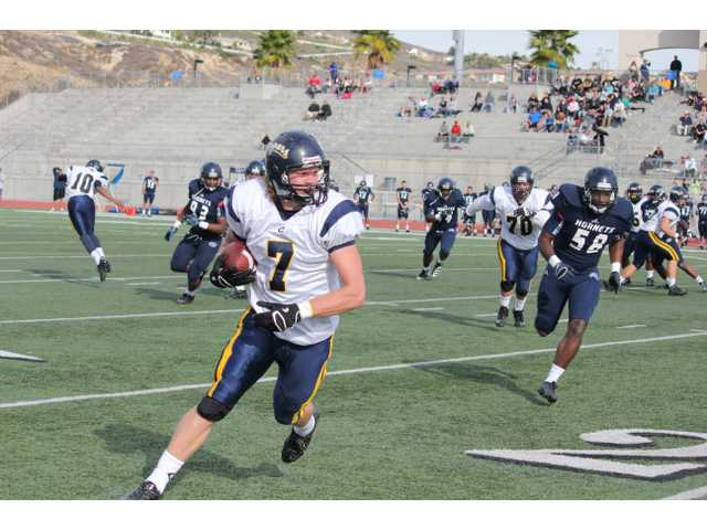 College of the Canyons tight end Dan Vear breaks away from Fullerton defenders on Saturday afternoon at Yorba Linda High School.