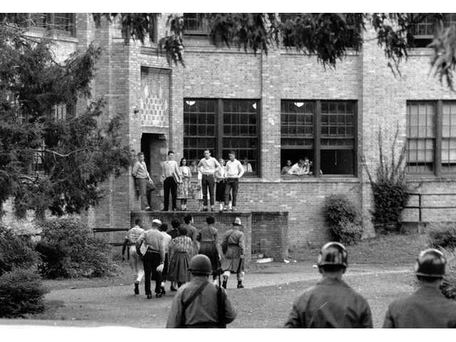 In this Oct. 15, 1957 file photo, seven of nine black students walk onto the campus of Central High School in Little Rock, Ark., with a National Guard officer as an escort and other troops watch.