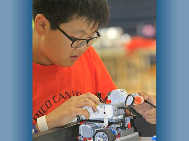 Brian No, 11, of Pico Canyon Elementary School, programs his team's robot in preparation for the final competition. Photo by John Lazar for The Signal.