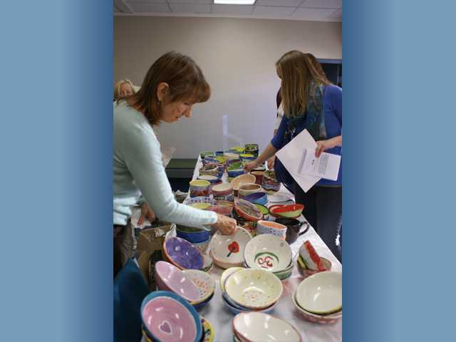 Bridge to Home volunteer Leslie Wenke, left, organizes hand-crafted soup bowls given to patrons of Sunday's Soup for the Soul fundraiser. Photo by Jim Holt.