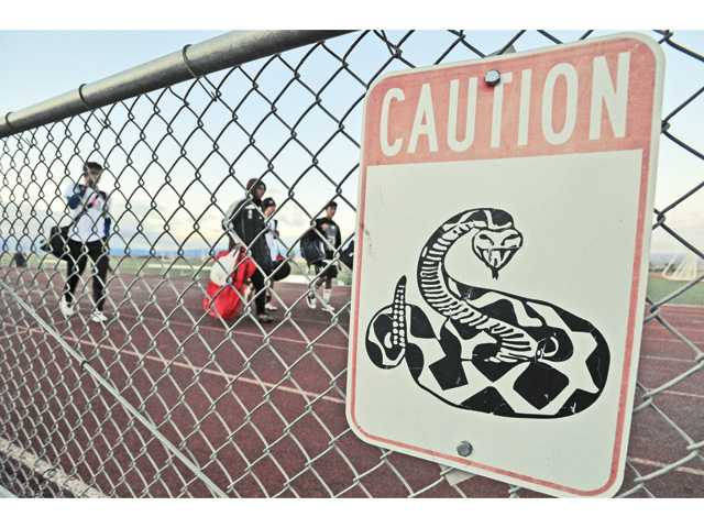 Members of the Golden Valley High School junior varsity soccer team walk past a rattlesnake caution sign posted on the track at Golden Valley High School. Photo by Signal photographer Dan Watson.