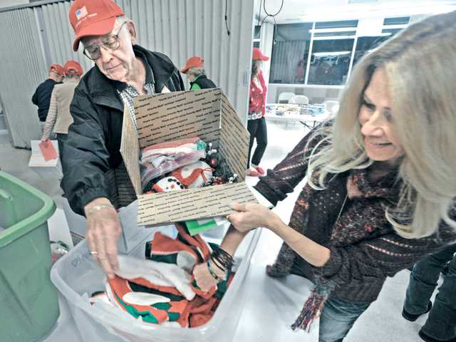 David Sowers, left, and Debbie Gardner join dozens of church volunteers as they fill shipping boxes with packages for the troops overseas at the Hands and Hearts event at Christ Luthern Church in Valencia. Signal photo by Dan Watson