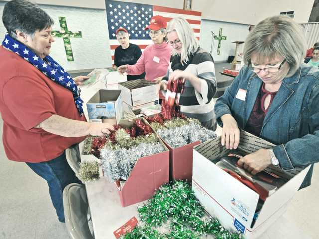 Event coordinator Karolle Blackson, left, and Rita Andrew join dozens of church volunteers as they fill shipping boxes with Christmas decorations for the troops overseas during the Hands and Hearts event at Christ Lutheran Church in Valencia. Signal photo by Dan Watson