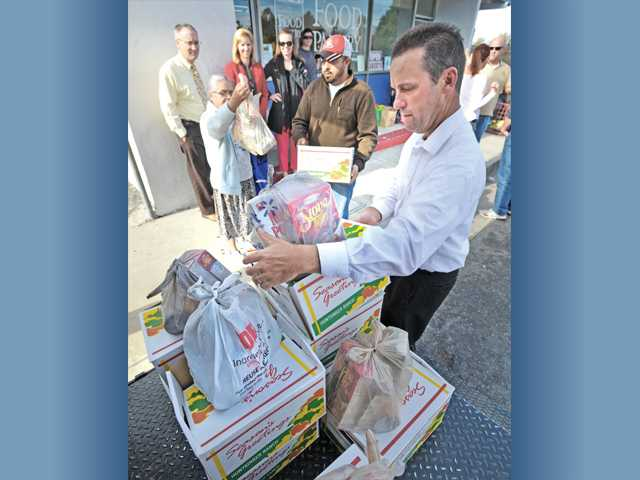 Senator Steve Knight, right, hands out frozen Thanksgiving turkeys and bags of trimmings to clients as they wait in line at the Santa Clarita Valley Food Pantry in Newhall  for some of the 400 Thanksgiving turkeys handed out on Tuesday morning. Photo by Charlie Kaijo.