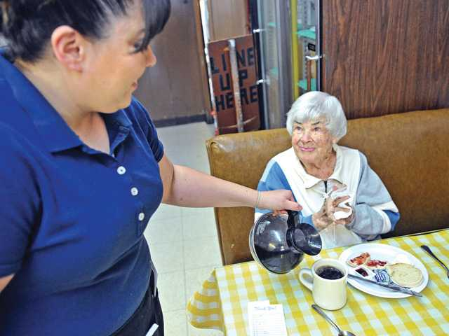 Waitress Norma Hernandez, left, pours coffee for Melba Fisher, 97, at the Way Station Coffee Shop in Newhall on Friday. Signal photo by Dan Watson.