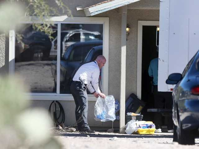 Tucson Police Department investigators and evidence technicians investigate the scene at a home where three girls had been imprisoned in Tucson, Ariz.