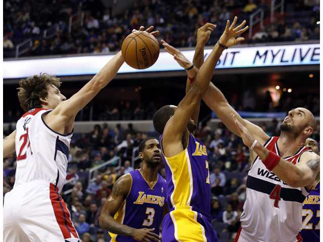 Washington Wizards forward Jan Vesely (24) and center Marcin Gortat (4) combine to block a shot by Los Angeles Lakers forward Xavier Henry (7) on Tuesday in Washington.