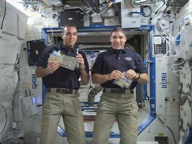 NASA astronauts Rick Mastracchio, left, and Mike Hopkins show some of the turkey and green bean casserole they plan to eat for their Thanksgiving meal.