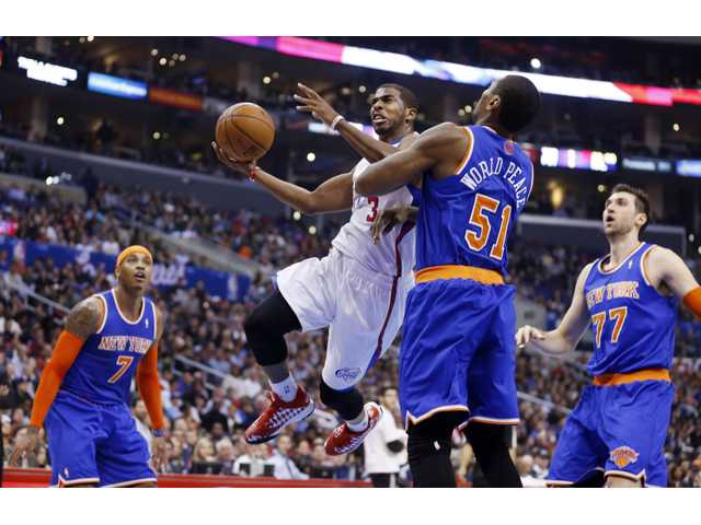 Los Angeles Clippers' Chris Paul (3) goes up to score past New York Knicks' Metta World Peace (51) on Wednesday. Paul left the game with a strained hamstring.