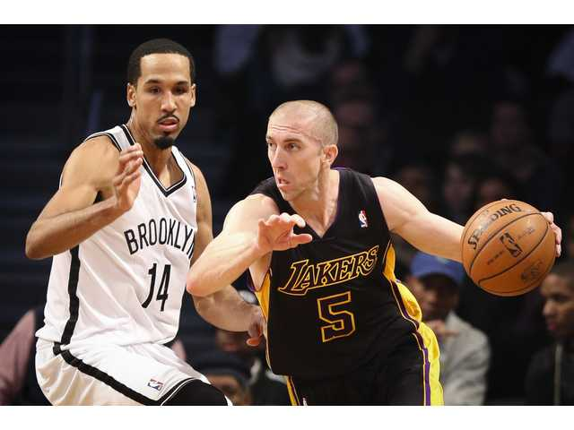 Los Angeles Lakers point guard Steve Blake (5) drives around Brooklyn Nets point guard Shaun Livingston (14) on Wednesday in Brooklyn, NY.