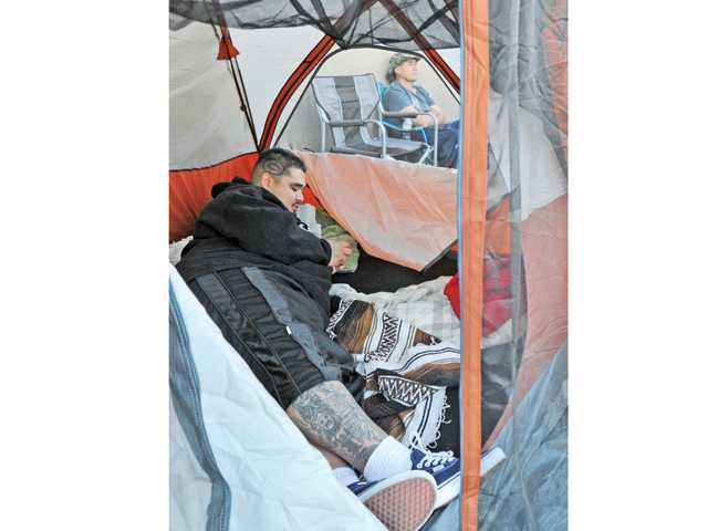 Camper Aaron Bugarin lays in his tent as Rene Bugarin of Canyon Country sits in a folding chair. They have been camped out in front the Best Buy store since last Sunday. Photo by Signal Staff Photographer Dan Watson.