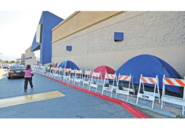 The tent line of pre-Black Friday bargain shoppers stretches out along the front wall of the Best Buy in Valencia, kept in check by parking barriers. Photo by Signal Staff Photographer Dan Watson.