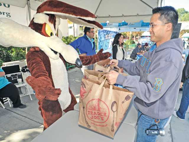 Cartoon character Wile E. Coyote, left, welcomes Pablo Manguy of Valencia as he drops off bags of food for the L.A. Regional Food Bank at the entrance to Six Flags Magic Mountain in return for free tickets for a day at the park on Wednesday morning. Photo by Dan Watson.