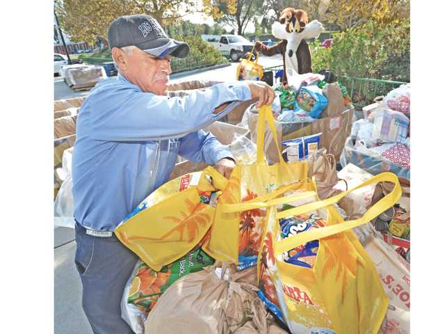 Francisco Valasquez, left, of the L.A. Regional Food Bank stacks bags of donated food onto a pallet at the entrance to Six Flags Magic Mountain in Valencia. Photo by Dan Watson.