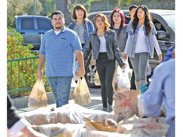 William Lopez, left, of Los Angeles and his family carry bags of food near the entrance to Six Flags Magic Mountain in Valencia. Photo by Dan Watson.