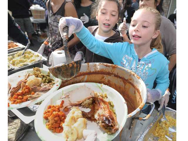 Emily Alber, 12, rear, looks on as Abby Morse-Tobeck, 9, ladles out chili as part of the annual Newhall Thanksgiving Feast held on Main Street Thursday. Photo by Dan Watson/The Signal.