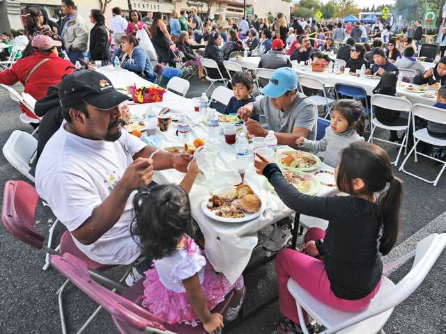 Families sit down at folding tables along Main Street in Newhall to enjoy a holiday meal at the annual Newhall Thanksgiving Feast. An estimated 3,000 attendees came to dinner this year. Photo by Dan Watson/The Signal.